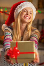 Girl in santa hat giving christmas present box Royalty Free Stock Photo