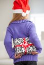 Girl in santa hat hiding christmas gift behind rear view of back at home Stock Images