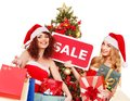 Girl in santa hat holding christmas gift box women sign saying sale and Stock Photography