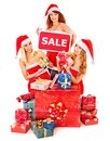 Girl in santa hat holding christmas gift box women sign saying sale and Stock Photos
