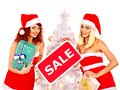 Girl in santa hat holding christmas gift box women sign saying sale and Stock Photo
