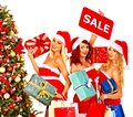 Girl in santa hat holding christmas gift box women sign saying sale and Royalty Free Stock Images