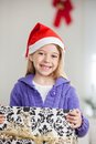 Girl in santa hat holding christmas gift portrait of smiling at home Royalty Free Stock Photography