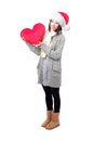 Girl in Santa hat holding heart pillow Royalty Free Stock Images
