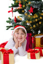 Girl in santa hat lying under christmas tree smiling Royalty Free Stock Photo