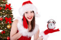 Girl in santa hat point on alarm clock by christmas tree isolated Stock Photos