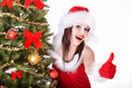 Girl in santa hat are showing thumb. Royalty Free Stock Photo