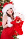 Girl in santa holding christmas sock and gift box. Stock Photo