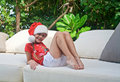 Girl in Santa's hat among tropical trees Royalty Free Stock Images