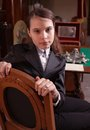 Girl sat in antique shop wearing pin striped suit on old wooden chair Stock Images