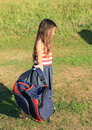 Girl with school bag in blue skirt and t shirt white and red stripes holding Royalty Free Stock Images