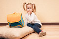 Girl with a school bag little sitting finger in her mouth on floor big near by horizontal studio shot Royalty Free Stock Photos