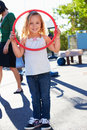 Girl in school playground with hoop looking to camera smiling Stock Photos
