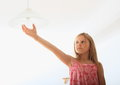Girl screwing bulb concentrated child on a lamp Stock Photography