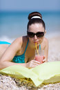 Girl at the sea attractive young woman lying on swimming mattress drinking juce from glass Stock Photography