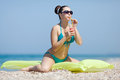 Girl at the sea attractive young woman sitting on swimming mattress drinking juce from glass Stock Photos