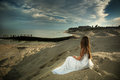 The girl and the sea a sitting on shore looks at Stock Photo