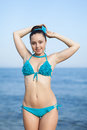 Girl at the sea young woman in bikini posing looking camera smiling Stock Image