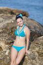 Girl at the sea young woman in blue swimwear posing on rocky seashore looking camera smiling Stock Photography