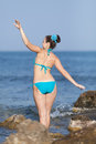 Girl at the sea young woman in blue swimwear on rocky seashore rear view Stock Images