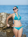 Girl at the sea young woman in sunglasses on rocky seashore looking camera smiling Royalty Free Stock Photos