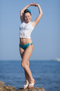 Girl at the sea young woman in white blouse and blue swimming trunks posing on seashore with hands raised Stock Images