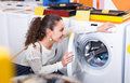 Girl selecting new washing machine Royalty Free Stock Photo