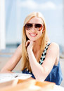 Girl in shades in cafe on the beach summer holidays and vacation Stock Images