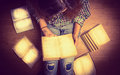 Girl in a shirt holding a book sitting on the floor around her spread open books close up  retro  toning Royalty Free Stock Photo