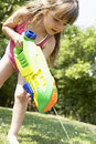 Girl shooting water pistol into the grass young in park Royalty Free Stock Photo