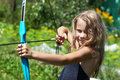 Girl shoots a bow on background of nature Stock Photo