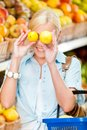 Girl at the shop choosing fruits hands lemons and vegetables and full of purchases hand cart Royalty Free Stock Photos