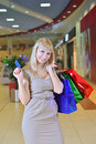 Girl with shopping bags and credit cards smiling in a store Stock Images