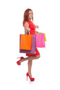 Girl with shopping bags full length side view of cheerful young woman in red dress holding and smiling while standing isolated on Royalty Free Stock Photos