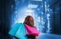 Girl with shopping bags looking at falling matrix in data center Royalty Free Stock Photography