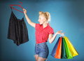 Girl with shopping bags retro style shopper woman happy buying clothes pinup holding olourful in one and rack clothes in Stock Photography