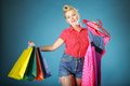 Girl with shopping bags retro style shopper woman happy buying clothes pinup holding olourful in one and rack clothes in Stock Photos