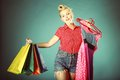 Girl with shopping bags retro style shopper woman happy buying clothes pinup holding olourful in one and rack clothes in Royalty Free Stock Photo