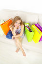 Girl with shopping bags on sofa Royalty Free Stock Image