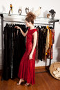 Girl shopping in boutique a red dress a clothing shop front of hanging fashion dresses Stock Images