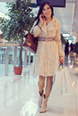 Girl in the shopping centre with shopping bags smiling young woman wearing beige coat speaking on phone and holding mall enjoy of Royalty Free Stock Photo
