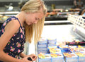 Girl shopping for food side view of blond frozen in supermarket Royalty Free Stock Photography