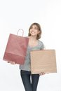 Girl and shopping lovely fair haired smiling keeping two packages in both hands thinking what she has bought isolated on the white Stock Photo