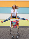 Girl with shopping trolley the happy the teenager joyfully jumps near to the cart full of purchases Royalty Free Stock Photography