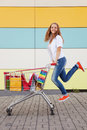 Girl with shopping trolley the happy the teenager joyfully jumps near to the cart full of purchases Stock Photos