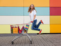 Girl with shopping trolley the happy the teenager joyfully jumps near to the cart full of purchases Royalty Free Stock Image