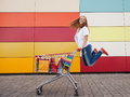 Girl with shopping trolley the happy the teenager joyfully jumps near to the cart full of purchases Stock Images