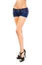 Girl in short shorts denim and black high heeled shoes great modeling figure the body of a young shapely legs slim waist Royalty Free Stock Photo