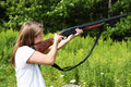 Girl with shotgun shooting skeet out in a field Stock Photos