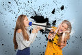 Girl shouting at another through megaphone on blue background with black paint splashes Stock Photo